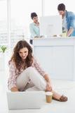 Femme d'affaires de sourire s'asseyant sur le plancher utilisant l'ordinateur portable Photo libre de droits