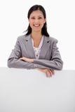 Femme d'affaires de sourire se penchant sur le mur blanc Images stock