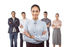 Femme d'affaires de sourire se tenant devant ses collègues avec des bras croisés Photographie stock