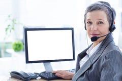 Femme d'affaires de sourire téléphonant et à l'aide de l'ordinateur Images stock