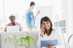 Femme d'affaires de sourire téléphonant et à l'aide du comprimé sur le sofa Image libre de droits