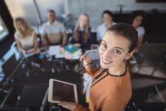 Femme d'affaires de sourire tenant le comprimé numérique avec des collègues dans le bureau photo stock