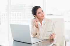 Femme d'affaires de sourire tenant le journal tout en travaillant sur l'ordinateur portable Photographie stock