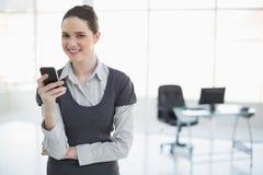 Femme d'affaires de sourire tenant sa pose de smartphone Image libre de droits