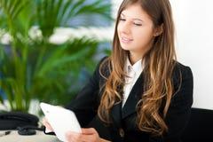 Femme d'affaires de Youngn à l'aide de sa tablette dans le bureau Photo libre de droits