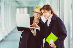 Femme d'affaires deux attirante de sourire à l'aide de l'ordinateur portable au lobby de bureau Photographie stock libre de droits