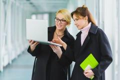 Femme d'affaires deux attirante de sourire à l'aide de l'ordinateur portable au lobby de bureau Photographie stock
