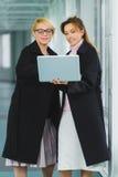 Femme d'affaires deux attirante de sourire à l'aide de l'ordinateur portable au lobby de bureau Images stock