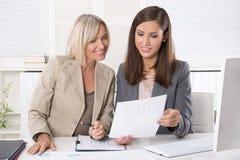 Femme d'affaires deux attirante s'asseyant dans un fonctionnement de bureau image stock