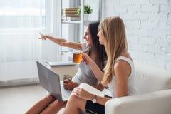 Femme d'affaires deux s'asseyant sur le sofa avec l'ordinateur portable Photographie stock libre de droits