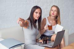 Femme d'affaires deux s'asseyant sur le sofa avec l'ordinateur portable Photographie stock