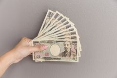 Femme d'affaires donnant l'argent et jugeant l'argent de 10.000 Yens japonais disponible sur le fond gris de mur, Yen japonais Photo libre de droits