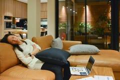 Femme d'affaires dormant sur le sofa dans le salon la nuit Photographie stock