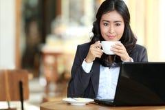 Femme d'affaires effectuant son travail tout en prenant une pause-café Photos libres de droits