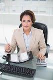 Femme d'affaires employant la calculatrice et le journal intime regardant l'appareil-photo Photographie stock