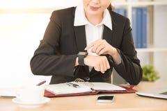 Femme d'affaires employant son application de smartwatch Image stock