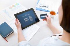 Femme d'affaires employant une carte de crédit pour des opérations bancaires en ligne d'Internet Photo libre de droits