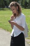 Femme d'affaires en stationnement envoyant un message avec texte Image stock