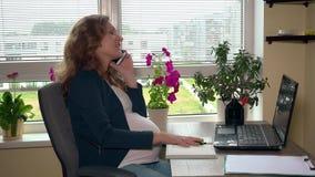 Femme d'affaires enceinte heureuse faisant des notes parlant au téléphone dans le bureau banque de vidéos