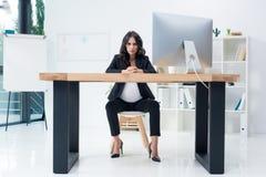 femme d'affaires enceinte sérieuse s'asseyant sur le lieu de travail Photo stock