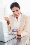 Femme d'affaires encourageante faisant des emplettes en ligne avec l'ordinateur portable photographie stock