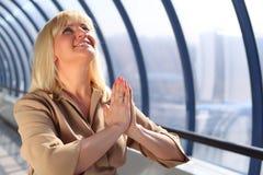 Femme d'affaires entre deux âges de prière photo stock