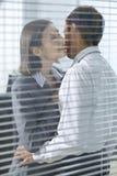 Femme d'affaires environ pour embrasser l'homme d'affaires dans le bureau Photos stock