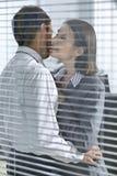 Femme d'affaires environ pour embrasser l'homme d'affaires dans le bureau Photos libres de droits