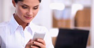 Femme d'affaires envoyant le message avec le smartphone se reposant dans le bureau Image stock