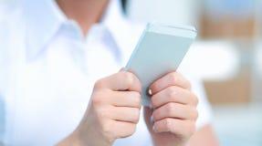 Femme d'affaires envoyant le message avec le smartphone se reposant dans le bureau Photographie stock