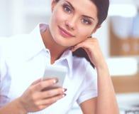 Femme d'affaires envoyant le message avec le smartphone se reposant dans le bureau photo stock