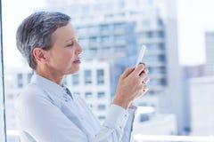 Femme d'affaires envoyant un message textuel Photos stock