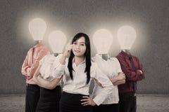 Femme d'affaires et équipe avec des têtes d'ampoule Photographie stock libre de droits