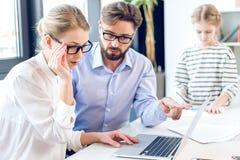 Femme d'affaires et homme d'affaires avec des lunettes fonctionnant avec l'ordinateur portable dans le bureau, petite fille derri photographie stock libre de droits