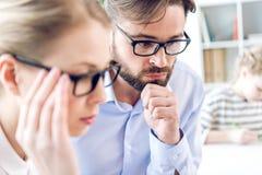 Femme d'affaires et homme d'affaires concentrés avec des lunettes fonctionnant dans le bureau Photos stock