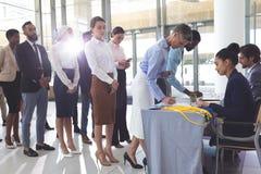 Femme d'affaires et homme d'affaires signant dedans à la table d'enregistrement de conférence images libres de droits