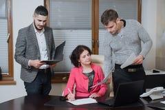 Femme d'affaires et ses secrétaires d'assistants dans son bureau Les secrétaires ont apporté les documents de patron pour signer photographie stock