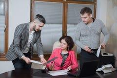 Femme d'affaires et ses secrétaires d'assistants dans son bureau Les secrétaires ont apporté les documents de patron pour signer images libres de droits