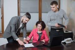 Femme d'affaires et ses secrétaires d'assistants dans son bureau Les secrétaires ont apporté les documents de patron pour signer image stock
