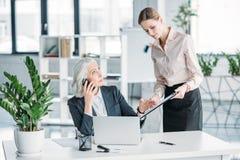Femme d'affaires et son patron travaillant avec l'ordinateur portable et les documents dans le bureau Image libre de droits