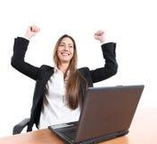 Femme d'affaires euphorique dans un bureau avec un ordinateur portable Photographie stock