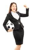 Femme d'affaires euphorique tenant un ballon de football et faire des gestes Image stock