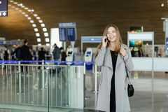 Femme d'affaires européenne parlant par le smartphone au hall d'aéroport, au manteau gris de port et au sac Photos libres de droits