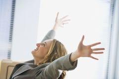 Femme d'affaires Excited s'asseyant dans le bureau Photos stock