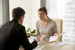 Femme d'affaires fâchée discutant avec l'homme d'affaires au sujet du fai d'écritures image libre de droits
