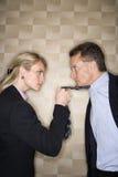 Femme d'affaires fâchée tirant la relation étroite de l'homme Images libres de droits