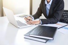 Femme d'affaires féminine intelligente travaillant sur l'ordinateur portable tandis qu'analysi Photo stock