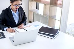 Femme d'affaires féminine intelligente travaillant sur l'ordinateur portable tandis qu'analysi Photos libres de droits