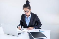 Femme d'affaires féminine intelligente travaillant sur l'ordinateur portable tandis qu'analysi Images libres de droits