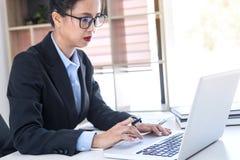 Femme d'affaires féminine intelligente travaillant sur l'ordinateur portable tandis qu'analysi Photos stock